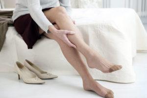 Массирует женские ноги