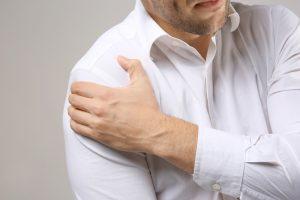 Мужчина массирует плечико