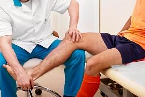 Терапевт осматривает ногу