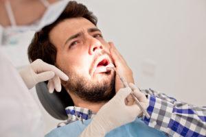 Мужчина сидит на стоматологическом кресле